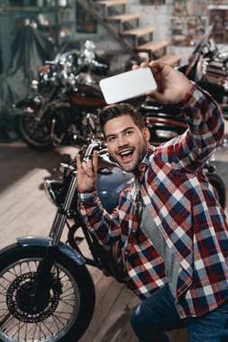Happy handsome man with rock sign taking selfie on smartphone with classic motorbike stock vector