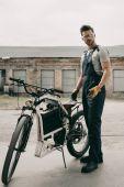 Fotografie Mechaniker mit Brille repariert Motorrad
