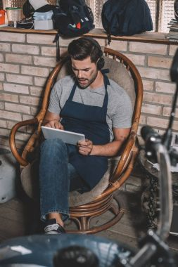 Mechanic with tablet and headphones