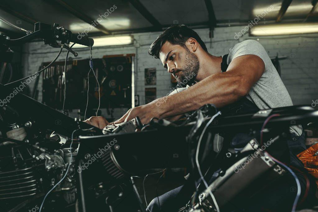 handsome mechanic repairing motorbike
