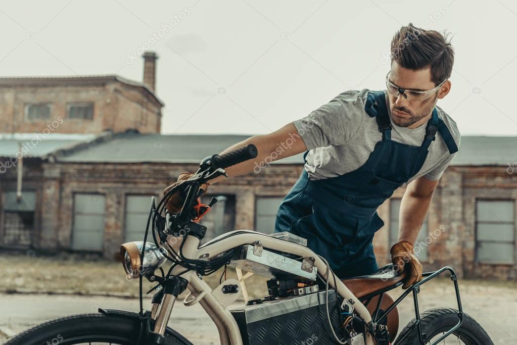 mechanic in goggles repairing motorcycle