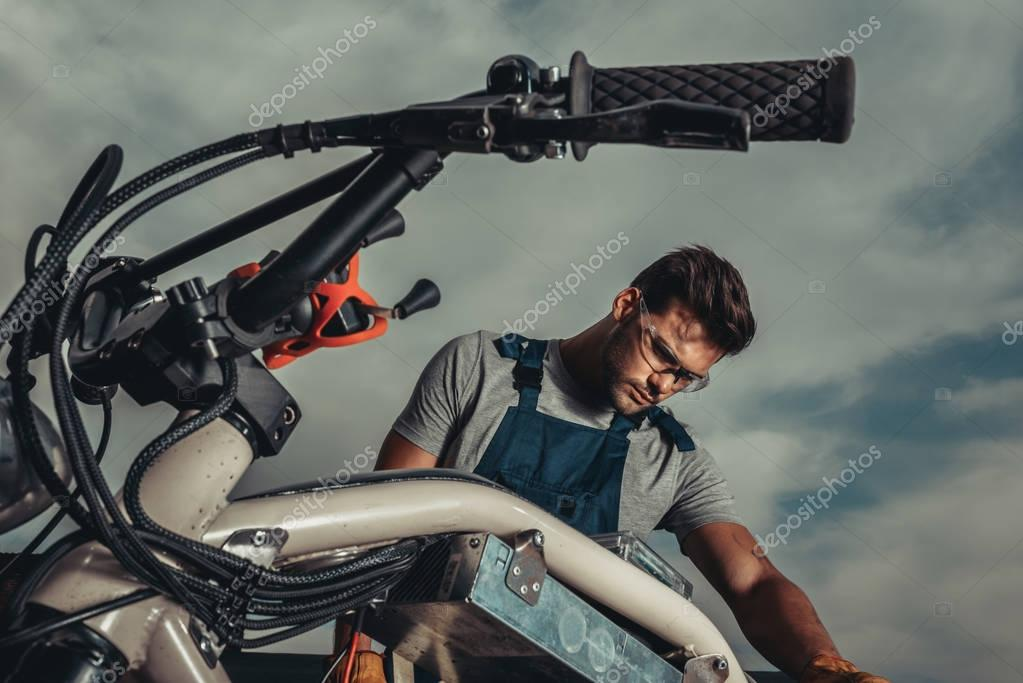 repairman in goggles with motorcycle