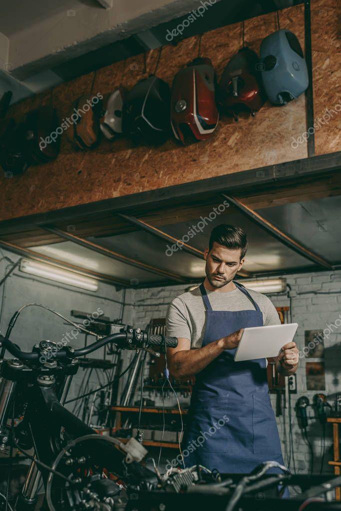 worker with tablet repairing motorcycle