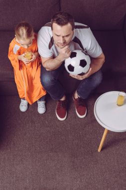 daughter and father watching football game