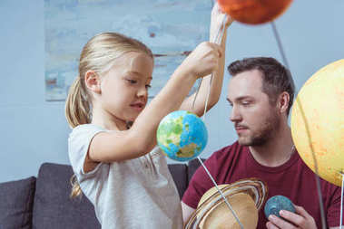 Father and daughter playing with planets