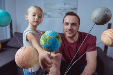 Daughter showing father model of Earth