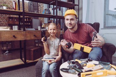 Father and daughter posing with toy tools
