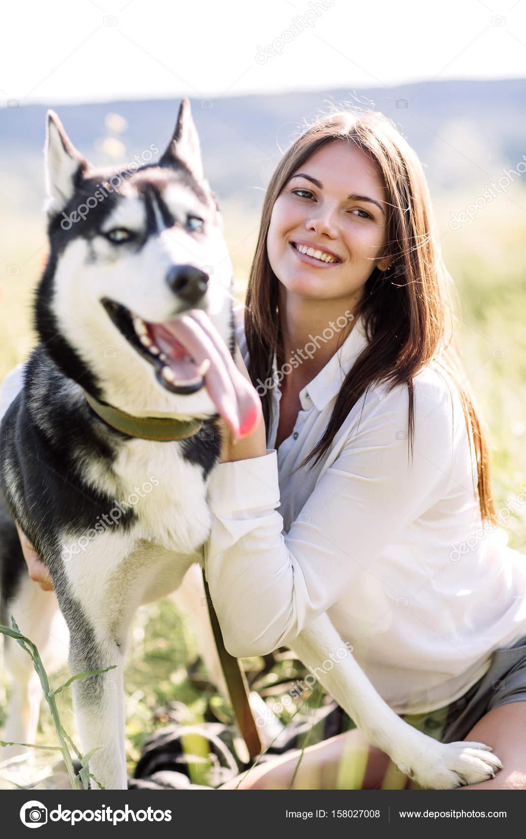 Bella ragazza gioca con un cane bianco e nero husky con gli occhi azzurri verde campo foto - Husky con occhi diversi ...