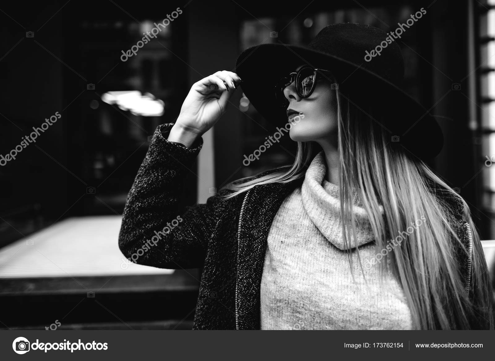 2990abe1ca8 Closeup portrait of a young beautiful fashionable woman wearing sunglasses.  A model in a stylish wide-brimmed hat– stock image