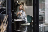 the girl at a table in a cafe drinks coffee, tea, looks out the window, is shot through glass, fashion