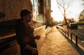 Young man smokes at sunset in the middle of the city