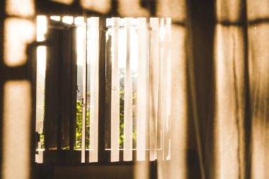 Morning sun shining through a window and wooden shutters onto mo