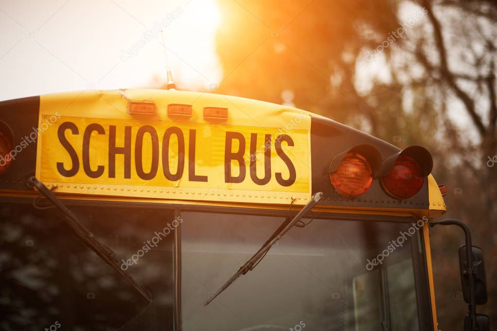Front closeup view of yellow school bus windshield sign at sunset