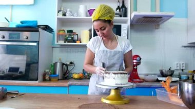 Girl smears the cream cake in the kitchen