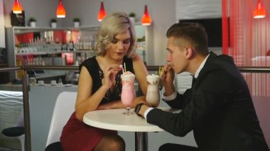 Man and woman drinking milkshakes at a cafe