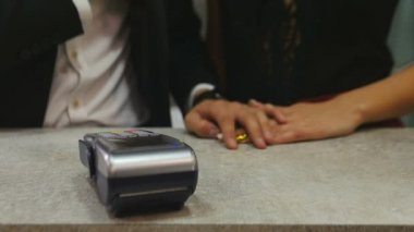 Close-up of a young man paying through smart phone using NFC technology