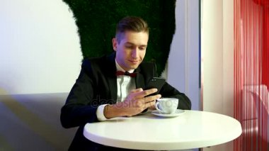 Young man in a suit sitting at table and using smartphone in a cafe