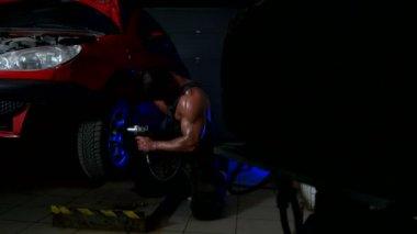 Sexy Guy Fixing the Wheel
