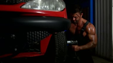 Sexy strong guy changes the wheel from car