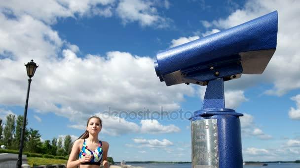 Sport lány fut fel az érme működő távcsövek, és úgy néz ki, rajta