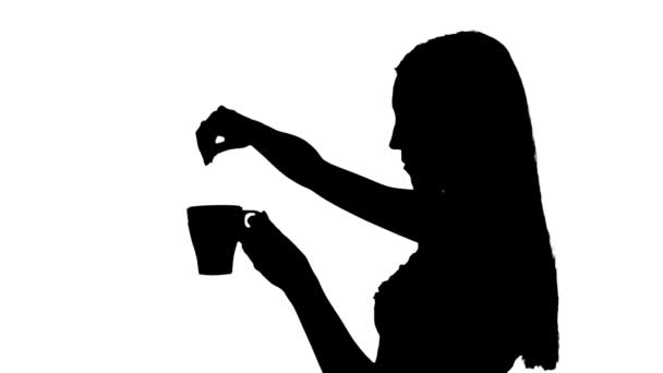 Woman putting tea bag into cup silhouette