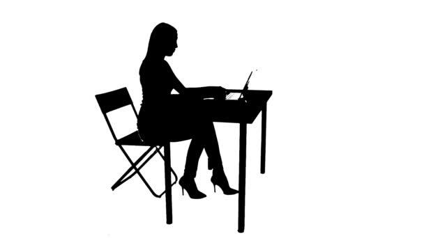 Žena sedí u stolu a použití notebooku silueta