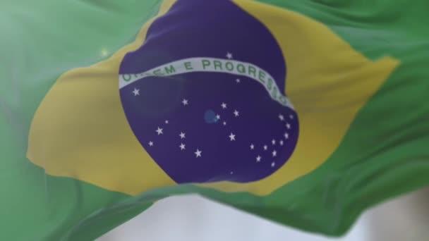 Brazilská vlajka pomalu mává. Zblízka brazilskou vlajkou mávající.