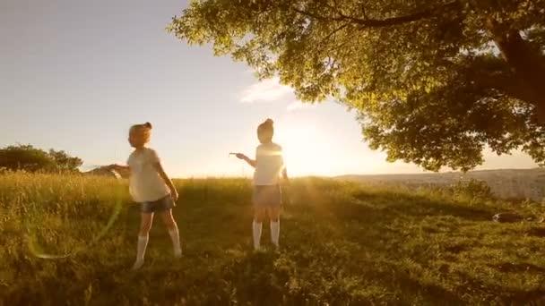 Two kids girls play with hula-hoop