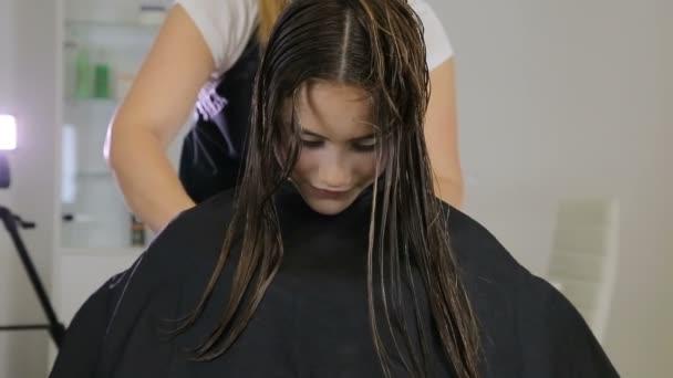 Kadeřník česání a řezání vlasy dospívající dívka klienta v kadeřnictví