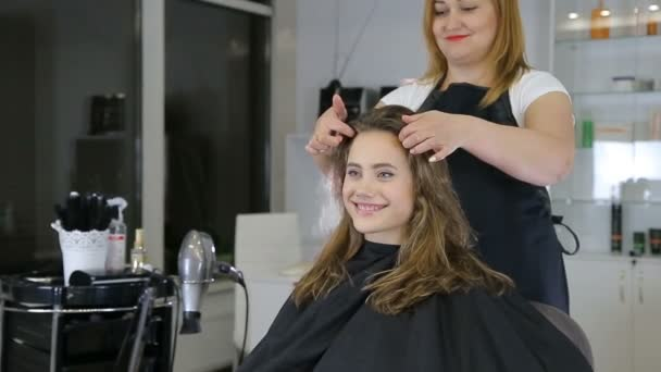 Professional hairdresser, stylist preparing hairstyle for teen girl using barrette for fixing hair