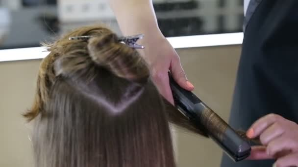 Professional hairdresser stylist curling up teen girl hair