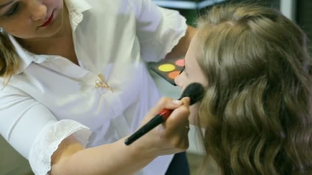 Professional makeup artist applying tonal powder to blond models skin.