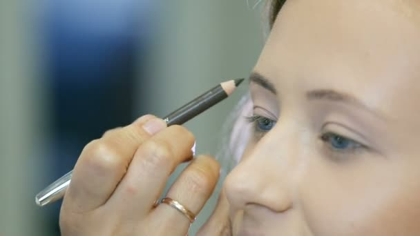 Professional makeup artist tones blond models eyebrow whith crayon.