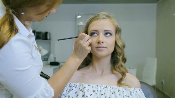 Profesionální vizážistka použití tužka na oči na blond modely víčko pro to víčko šipky