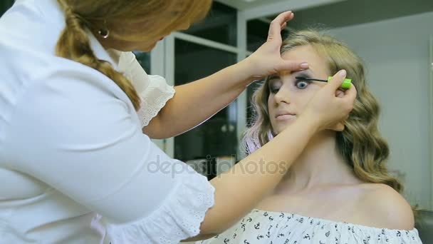 Professional makeup artist applying mascara to blond models eyelashes.