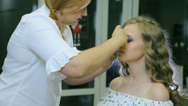 Professional makeup artist attaches artificial eyelashes to blond models eyelid.