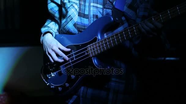 Rockový hudebník hraje basovou kytaru na koncertě.