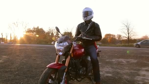 Mladý muž v černé kožené bundě a bílá helma sedí na motorce klade na ochranné rukavice před cestou na podzimní západ slunce