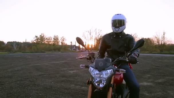 Mladý muž v černé kožené bundě a bílá helma sedí na motorce zapne světla před cestou na podzimní západ slunce