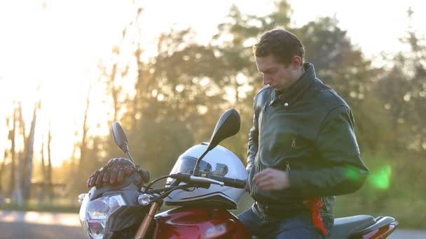 Egy fiatal férfi fekete bőr kabát ül a motorkerékpár, hozza ki napszemüvegek, és hozza a fehér sisak utazás: őszi naplemente előtt