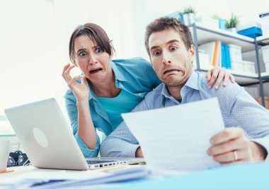 Stressed young couple checking bills
