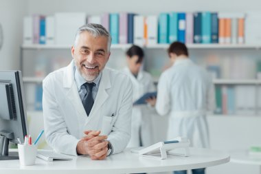 Confident doctor at reception desk