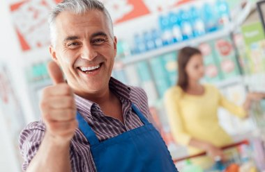 Supermarket clerk showing thumb up