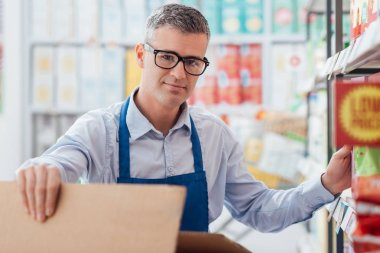 Supermarket clerk sorting items on shelf