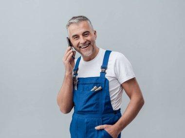 Repairman talking on smartphone