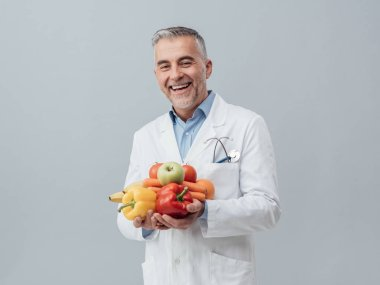 nutritionist holding fresh vegetables and fruits