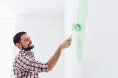 smiling man painting walls in apartment