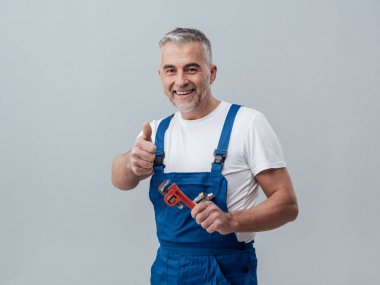 Cheerful repairman holding adjustable wrench