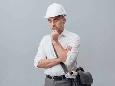 Thoughtful construction engineer with hand on chin