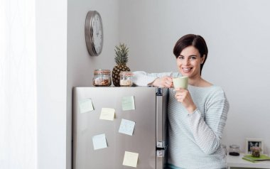 Young woman leaning on fridge